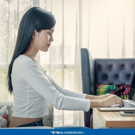 Immagine di una ragazza seduta con la schiena dritta davanti al pc