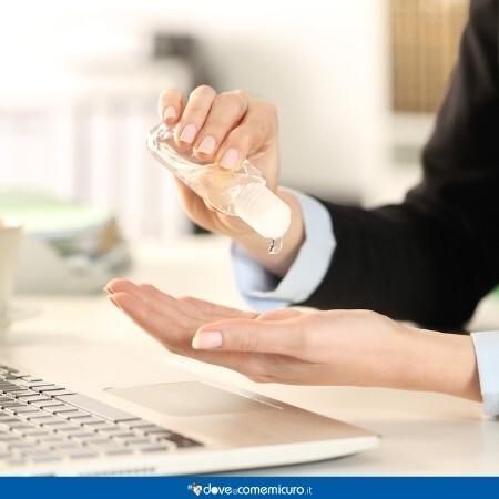 Immagine infografica che rappresenta una donna in ufficio che si igienizza le mani con il gel
