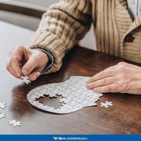 Immagine che rappresenta un uomo seduto al tavolo a comporre un puzzle di un profilo umano della testa