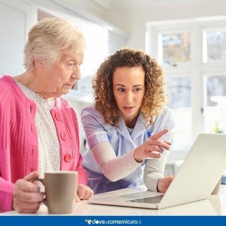 Immagine che rappresenta un'anziana signora insieme ad un operatore sanitario che guardano lo schermo del pc