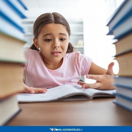 Immagine che rappresenta una bambina in difficoltà con lo studio tra due pile di libri