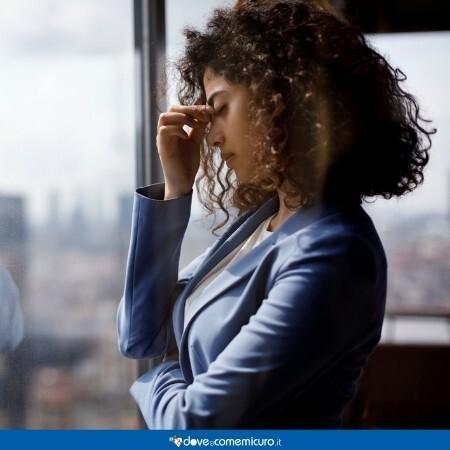 Immagine che rappresenta una donna che soffre di emicrania al lavoro dopo un viaggio lungo