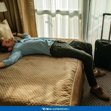 Immagine che rappresenta un uomo stanco dopo il viaggio lungo disteso sul letto