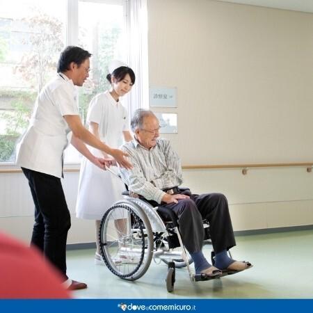 Immagine che rappresenta un paziente in carrozzina assistito da due operatori sanitari