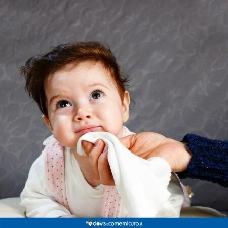 Immagine che rappresenta un neonato al quale la mamma sta pulendo il vomito dalla bocca