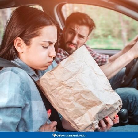 Immagine che rappresenta una donna che ha un conato di vomito in macchina