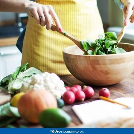 Immagine che rappresenta una donna che prepara un'insalata con verdure sul tavolo