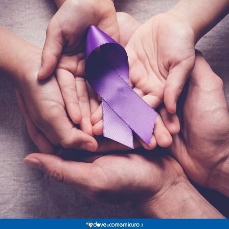 Immagine che rappresenta delle mani che reggono il fiocco viola