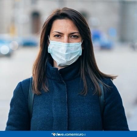 Immagine che rappresenta una donna con una mascherina chirurgica in città