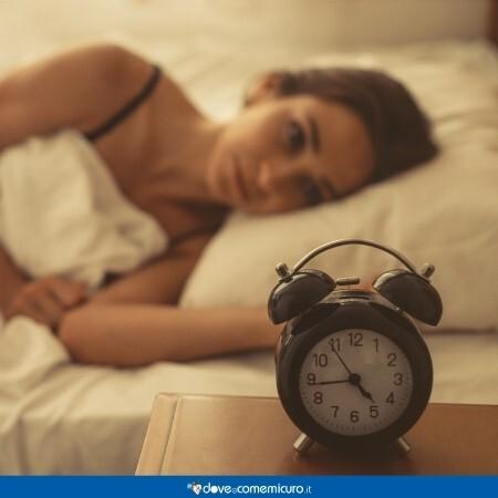 Immagine che rappresenta una donna che soffre d'insonnia a letto con un orologio in primo piano