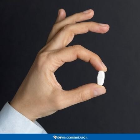 Immagine che rappresenta la mano di un uomo che regge una compressa