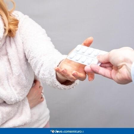 Immagine che rappresenta una donna che prende un farmaco per il dolore di stomaco