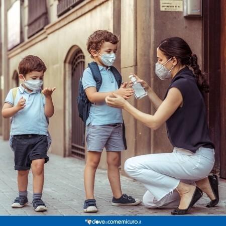 Immagine che rappresenta una mamma che igeinizza le mani ai figli