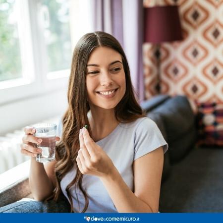 Immagine che rappresenta una donna che assume un integratore per via orale