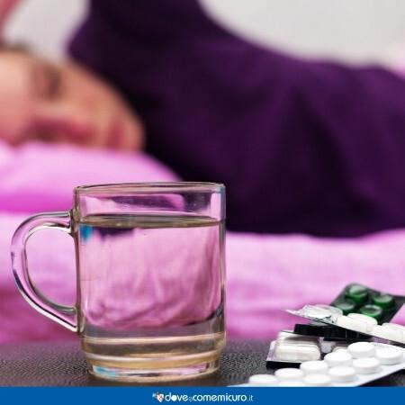 Immagine che rappresenta una persona malata e in primo piano i farmaci per curarsi