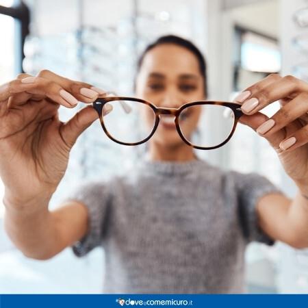 Immagine che rappresenta una donna con degli occhiali da vista in mano
