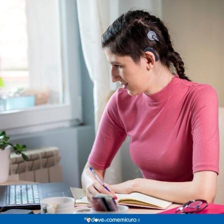 Immagine che rappresenta una donna che sta lavorando al pc con un impianto cocleare