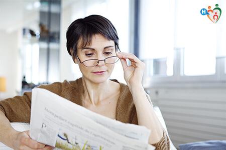 Donna che legge il giornale indossando un paio di occhiali da vista