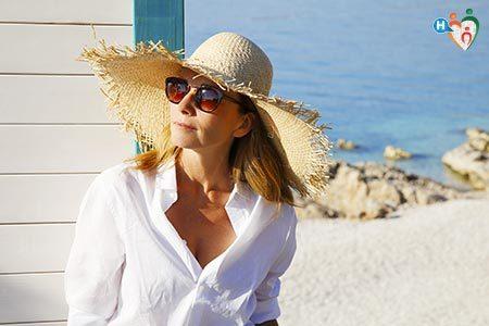 Donna al mare con occhiali da sole per proteggersi dai raggi UV