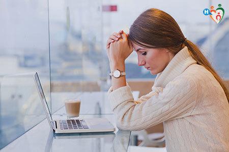 Donna seduta al tavolo davanti al computer con aria preoccupata