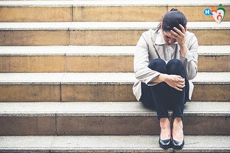 Donna seduta su una scalinata con aria pensierosa e disperata