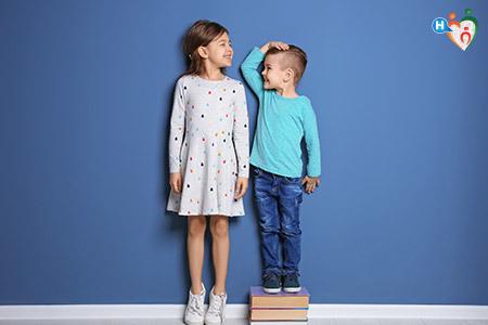 """Altezza dei bambini. Due bambini che si """"misurano"""" in altezza"""
