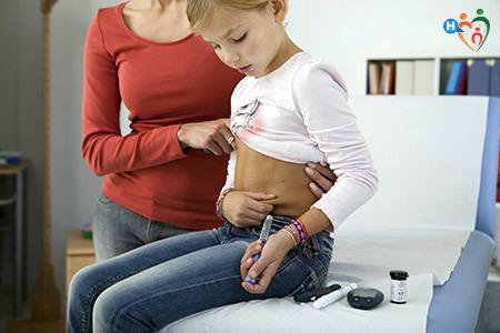 Mamma insegna ad una bambina come fare l'iniezione per l'insulina