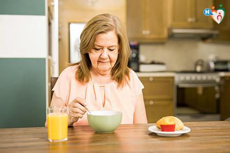 Signora che fa colazione, seduta al tavolo della cucina