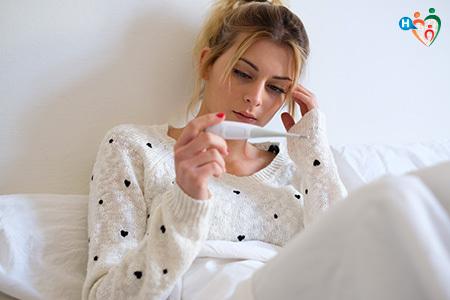 Immagine che mostra una ragazza sofferente nell'atto di misurarsi la febbre