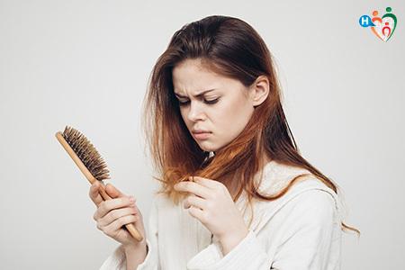 Immagine che mostra una ragazza nell'atto di pettinarsi che sta perdendo molti capelli