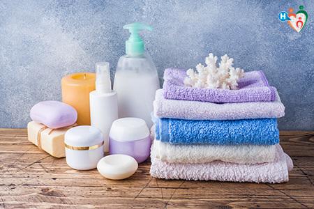 immagine che ritrae asciugamani e saponi appoggiati ordinatamente sopra una mensola di legno del bagno
