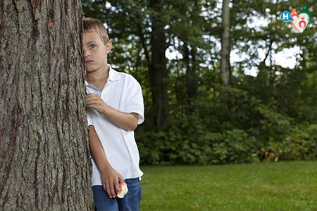 Immagine dove c'è un bambino timido, che si nasconde dietro un albero