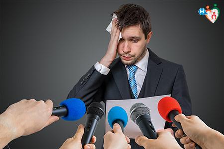 Immagine dove c'è un ragazzo che deve parlare in pubblico davanti a dei microfoni ma è in ansia e sta sudando freddo