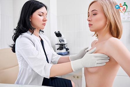 Immagine di dottoressa che visita una paziente verificando la presenza di noduli o cisti palpando il seno