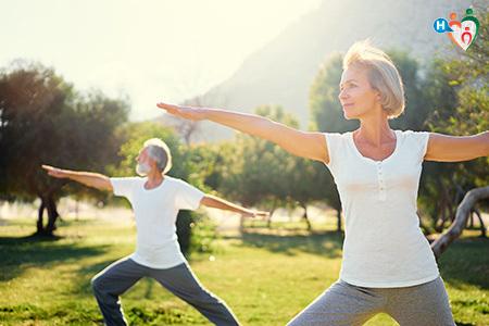 immagine che ritrae marito e moglie sui 60 anni mentre fanno yoga in un parco