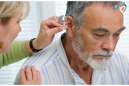 Immagine che mostra una dottoressa inserire nell'orecchio del paziente l'apparecchio acustico