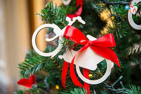 Immagine con un addobbo per l'albero di natale a forna di bicicletta stilizzata di legno con un fiocco rosso.