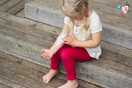 Immagine di bambina mentre si spalma una crema bianca sul braccio.