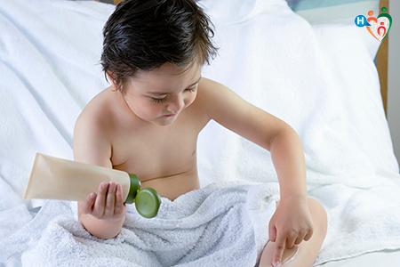 Immagine che ritrae bambino mentre si spla la crema idrante dopo la doccia, seduto sul lettone