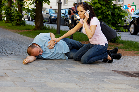 Immagine che mostra una donna prestare soccorso a un uomo sdraiato a terra per strada in preda a una crisi epilettica.