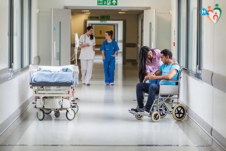 Immagine che rappresenta una corsia di un ospedale con infermieri che camminano e un'infermiera che aiuta un malato