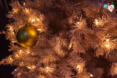 immagin che mostra un dettaglio di un albero di natale bianco con palline oro e luci intermittenti