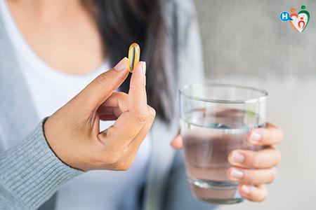 Immagine che mostra una donna con in mano una pillola e nell'altra un bicchiere d'acqua
