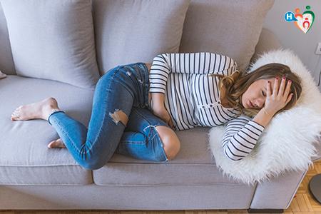 Immagine che ritrae una giovane donna sdraiata sul divano in preda agli spasmi