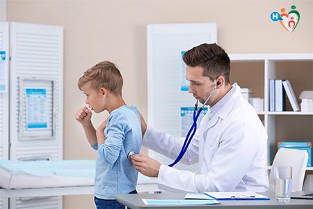 immagine che ritrae un medico mentre visita un bambino che tossisce