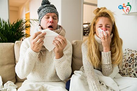 immagine dove due amici seduti sul divano starnutiscono insieme, in preda al raffreddore