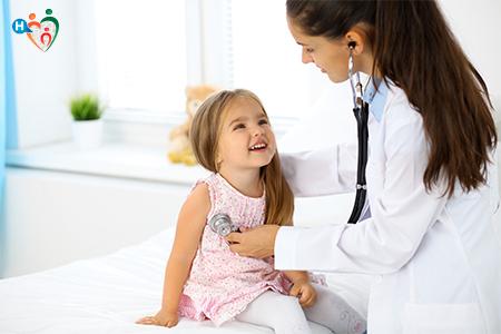 Immagine che mostra una pediatra mentre visita una bambina in uno studio tutto bianco e luminoso