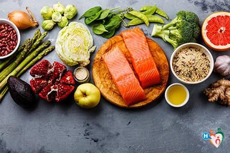 L'immagine mostra una serie di alimenti contenenti acido folico e quindi vitamina b9: salmone, asparagi, melograno, cereali, spinaci