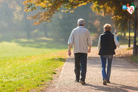 Immagine che mostra due anziani che passeggiano in un parco assolato
