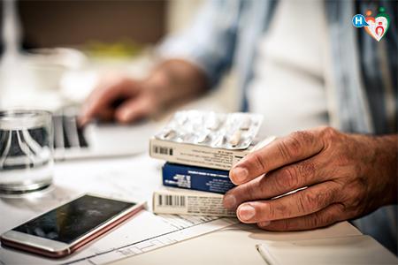 immagine che mostra il tavolo di un dottore dove sono appoggiate delle pillole e uno smartphone